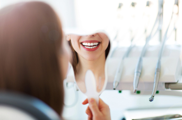 Woman looking at her smile in a mirror after getting dental implants at Watermark Dentistry in Normandy Park, WA